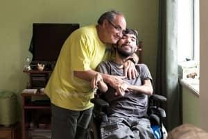 Pai assiste aulas e ajuda filho com paralisia a se formar jornalista 1