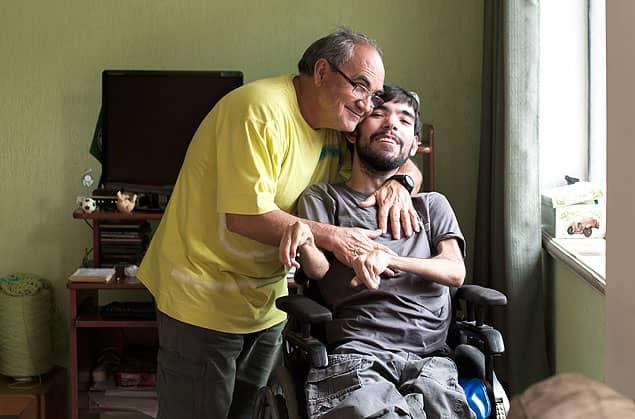Pai assiste aulas e ajuda filho com paralisia a se formar jornalista 3