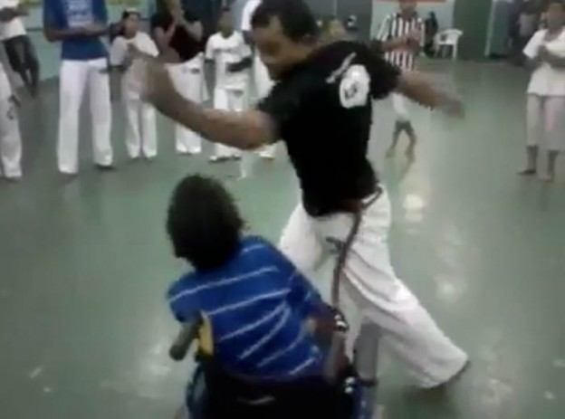 Professor luta capoeira com aluno com deficiência motora 2