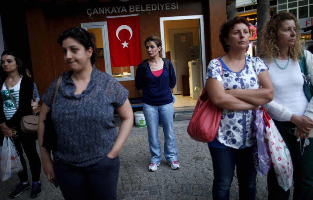 People stand in silence during a protest at Kugulu park in central Ankara