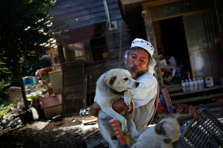 Image: Keigo Sakamoto holds Atom, one of 21 dogs and over 500 animals he keeps at his home in the exclusion zone near Naraha in Fukushima prefecture