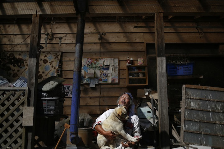 Keigo Sakamoto (58), holds Atom one of his 21 dogs and over 500 animals he keeps at his home in the exclusion zone near Naraha
