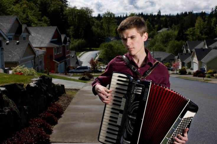 Ethan, practicing his accordion outside his home in Port Orchard, Washington