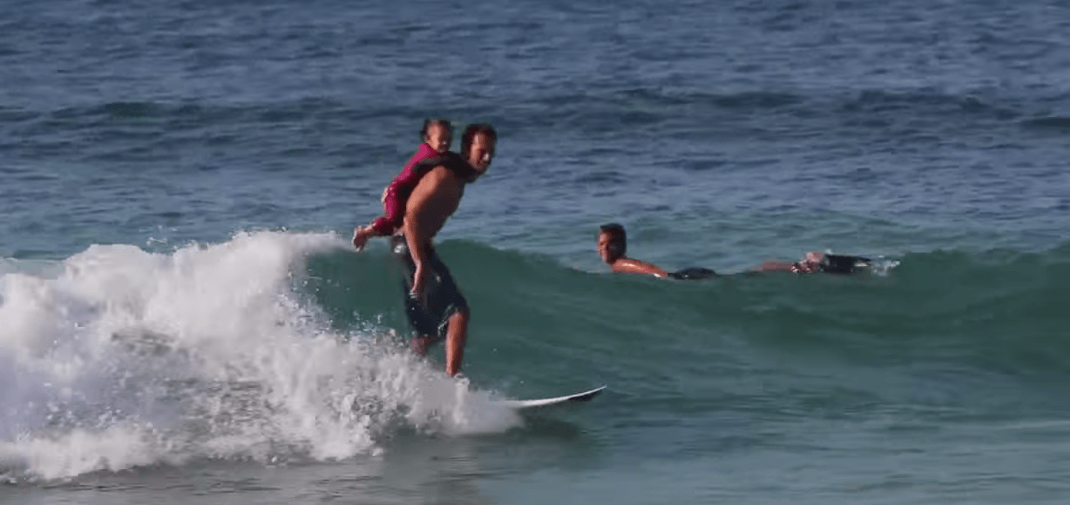 Pai surfista leva filha para pegar onda junto com ele, nas costas 1