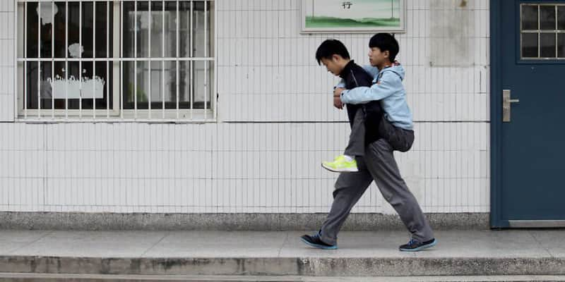 Há 3 anos estudante leva amigo que sofre de distrofia muscular todo o dia para escola nas costas 1