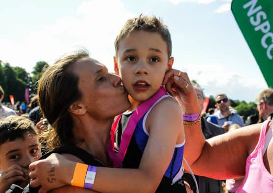 Bailey Matthews  8 from Doncaster  gets a kiss from his mother  Julia  after he crossed the finish line  to complete his first ever triathlon at Castle Howard on sat.