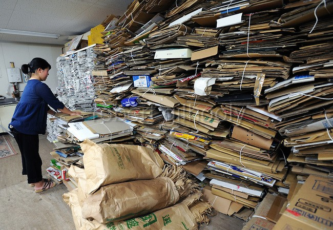 A resident disposes of cardboard boxes at the waste disposal site in central Kamikatsu Town in Shikoku, Japan. The town, whose residents number just over 2,000 people, has implemented a waste recycling policy that aims at eliminating waste entirely within the next 12 years and employs retired local residents to care for the waste disposal center. Waste must be divided up into 34 categories. Photographer: Robert Gilhooly