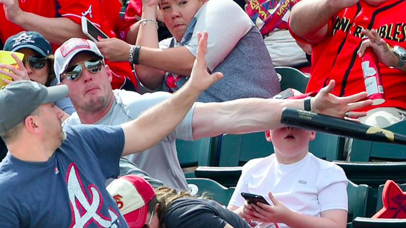 Homem salva criança distraída com celular de ser atingida por um taco de baseball 2