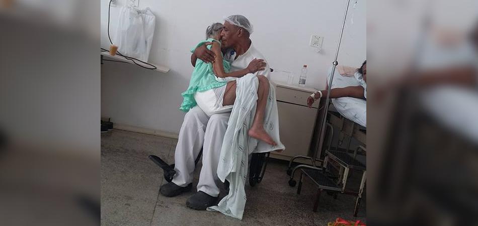 Maqueiro canta para amenizar as dores e acalmar paciente idosa, segurando-a no colo 2