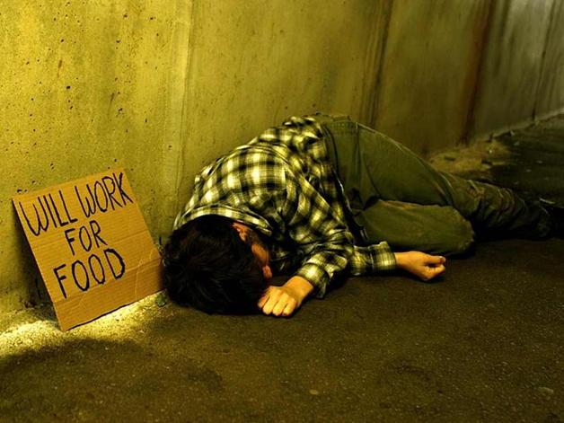 """Morador de rua na Europa. """"Trabalho por comida"""", diz o cartaz"""