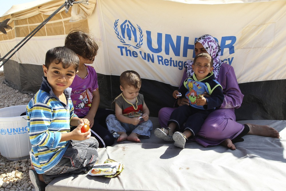Image: A Syrian refugee woman sits with her children during a visit by UNHCR Guterres and Jordan's Foreign Minister Judeh to the Al Zaatri refugee camp in Mafraq