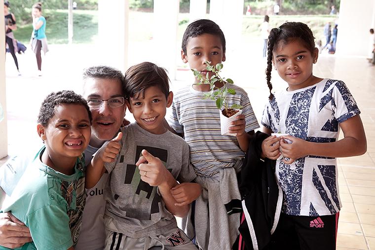 Voluntário PepsiCo com crianças atendidas pela Liga Solidária na oficina de plantio de mudas.