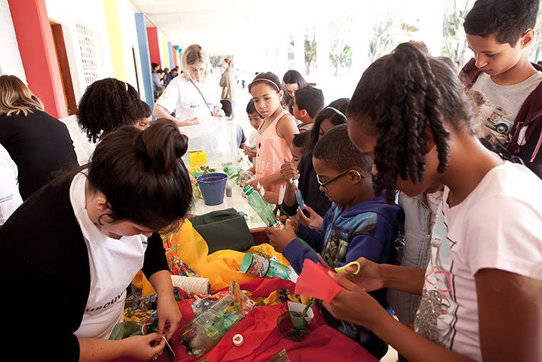 Voluntários PEPSICO com crianças atendida pela Liga Solidária em oficina de reciclagem.