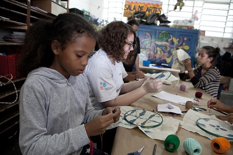 Voluntário PEPSICO com crianças atendida pela Liga Solidária em oficina de arte.
