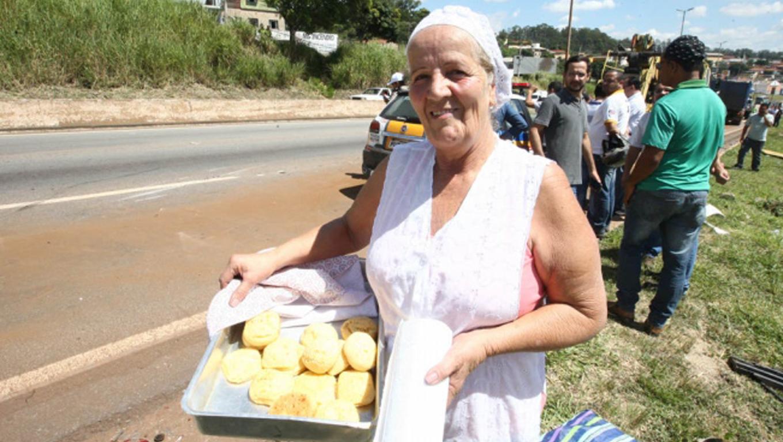 senhora distribui pão de queijo