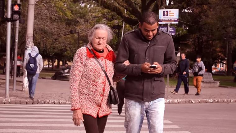 Para alertar sobre o perigo da desatenção causada pelo celular, mulher de 82 anos ajuda pedestres a atravessar a rua 1
