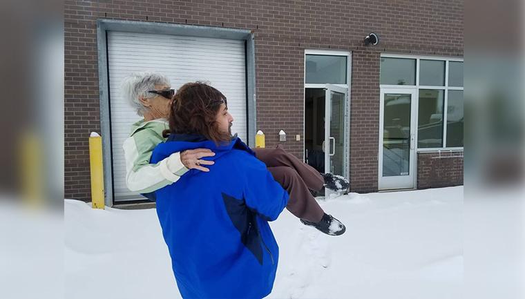 Médico abre consultório e carrega paciente no colo pelo estacionamento com neve 2