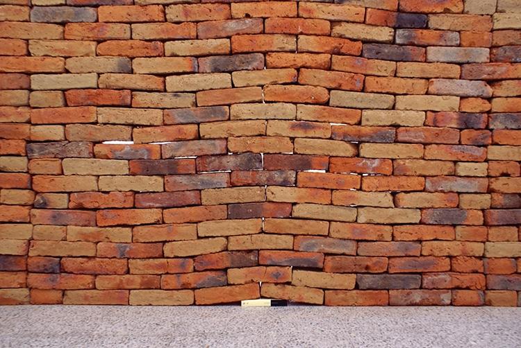 Instalação revela o poder metafórico de um único livro distorcendo um muro de tijolos 3