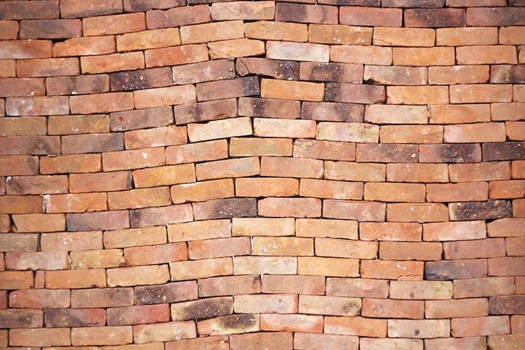 Instalação revela o poder metafórico de um único livro distorcendo um muro de tijolos 5
