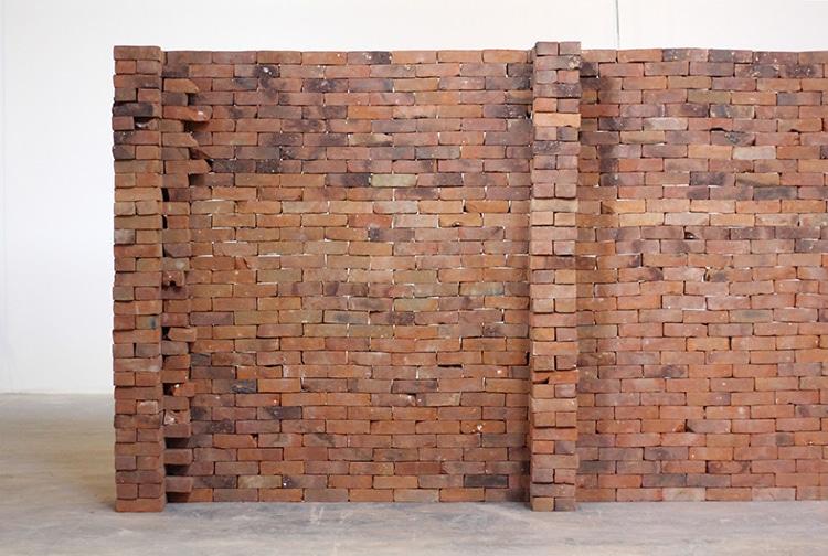 Instalação revela o poder metafórico de um único livro distorcendo um muro de tijolos 6