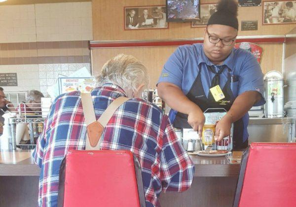 garçonete ajuda idoso a comer