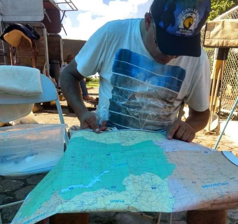 homem-sentado-boné-lê-mapa-viagem