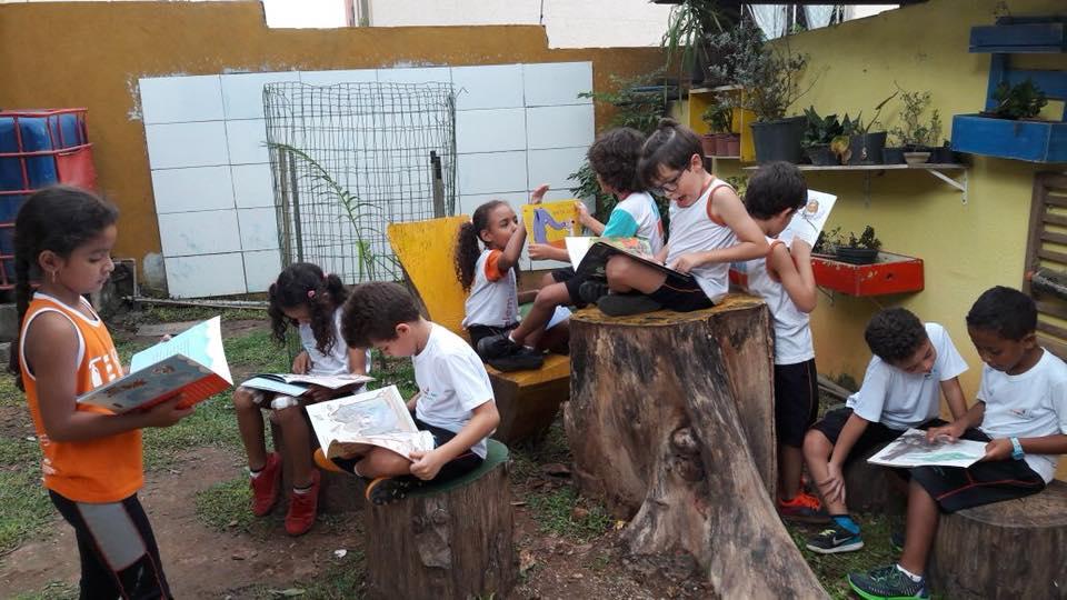 criança lendo debaixo de árvore escola