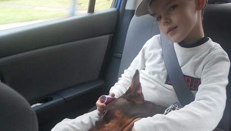 garoto abraçando cachorro dentro carro