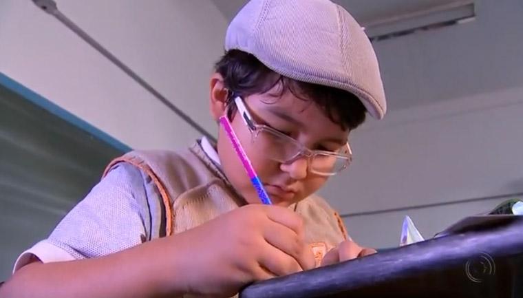 menino desenha figurinhas álbum copa mundo