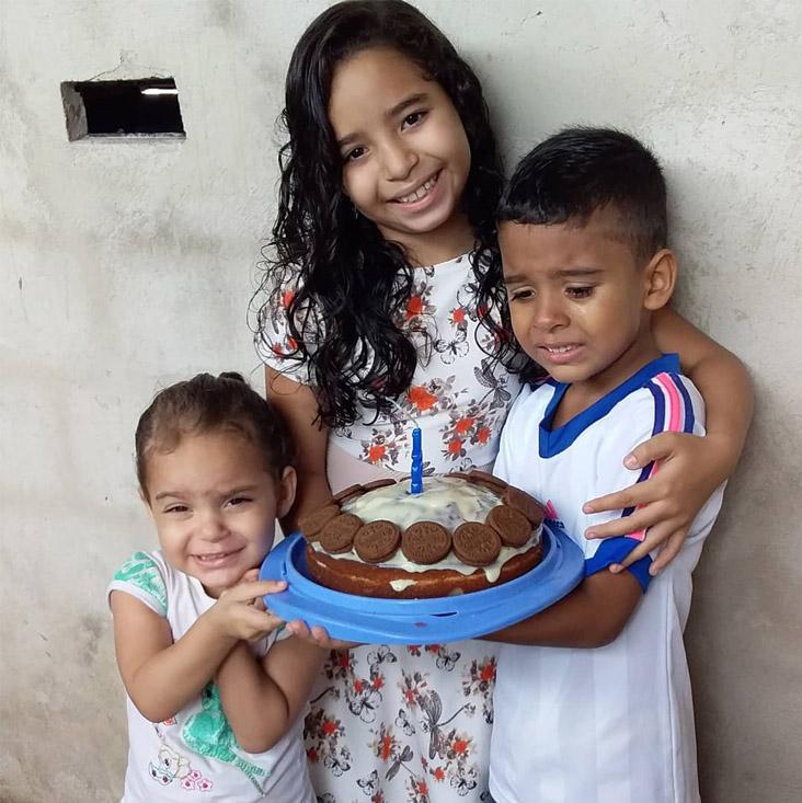 menina aniversário surpresa irmão bolo presentes