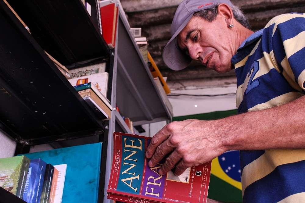 homem transforma comodo biblioteca comunitária