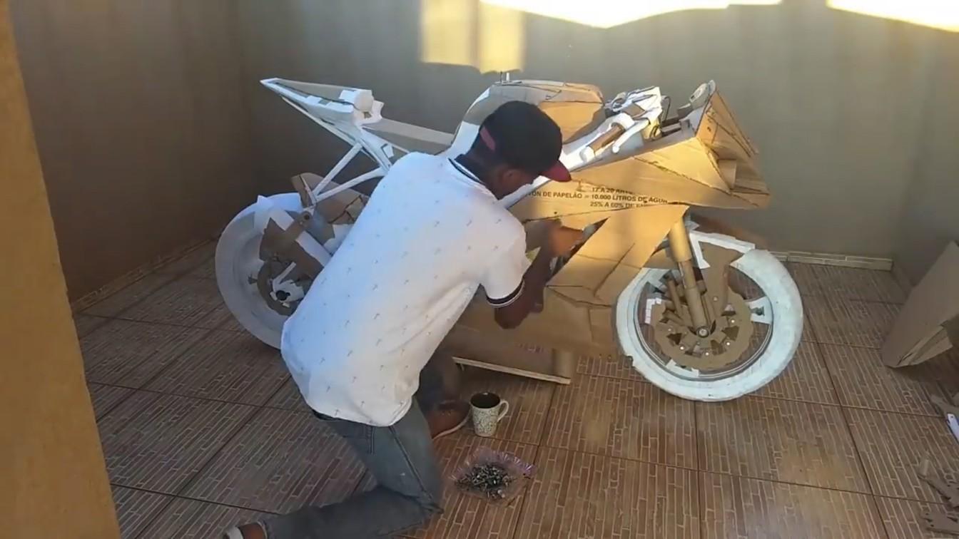 jovem monta moto papelão