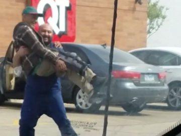 homem carrega idoso colo carro