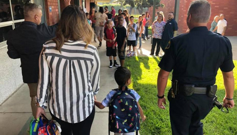menino escoltado policiais primeiro dia escola