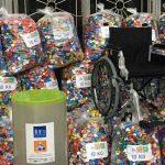 Cadeira de rodas sobre montanha de tampinhas plásticas