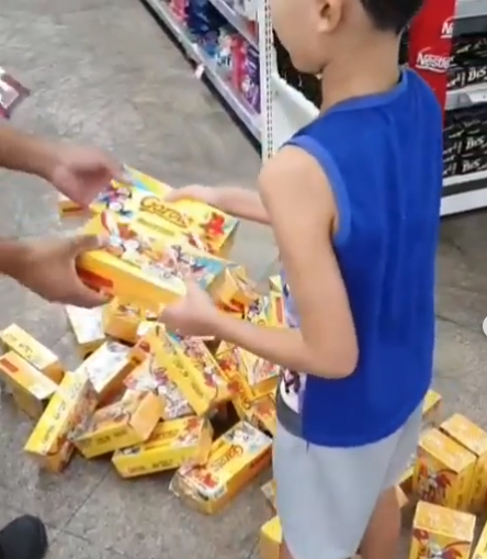 menino ajuda funcionário recolher caixas de bombom chão