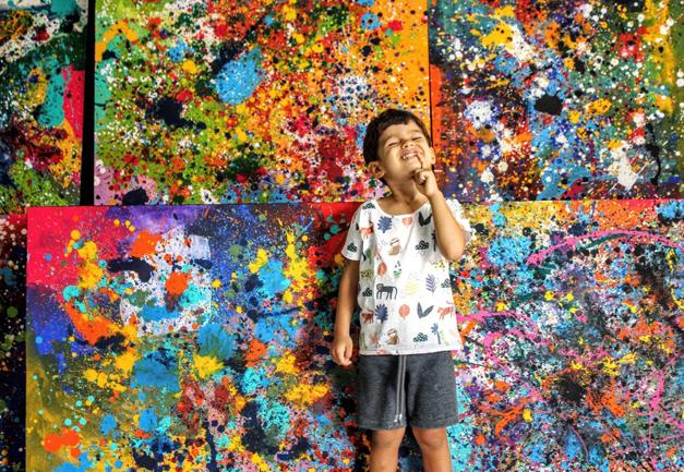 Garoto autista em frente a telas coloridas que ele pintou