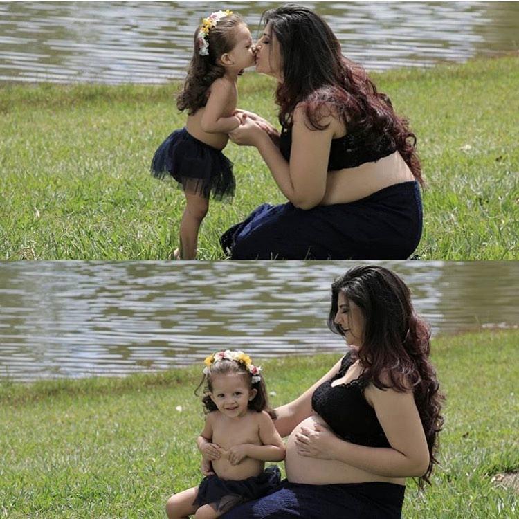 mulher grávida brincando filha beira lago