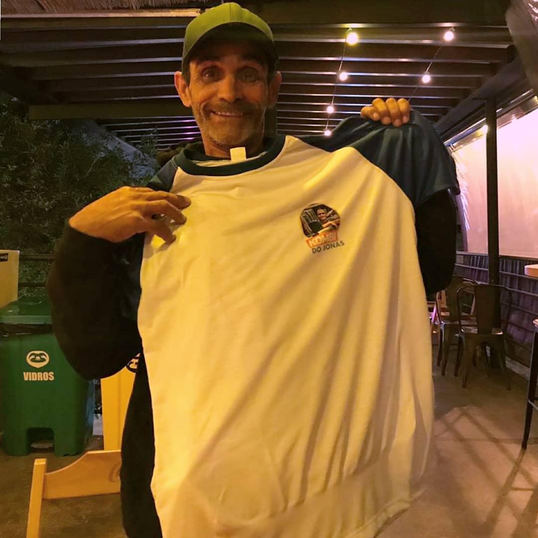 homem boné segurando camiseta