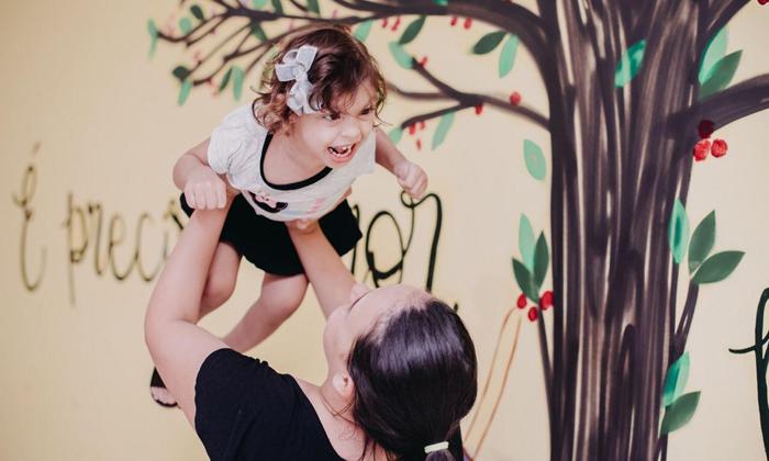 mãe levantando filha microcefalia