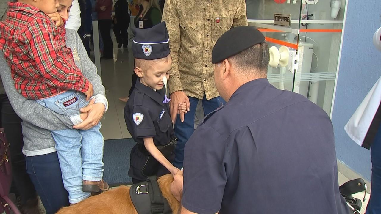menino vestido policial cumprimentando policial
