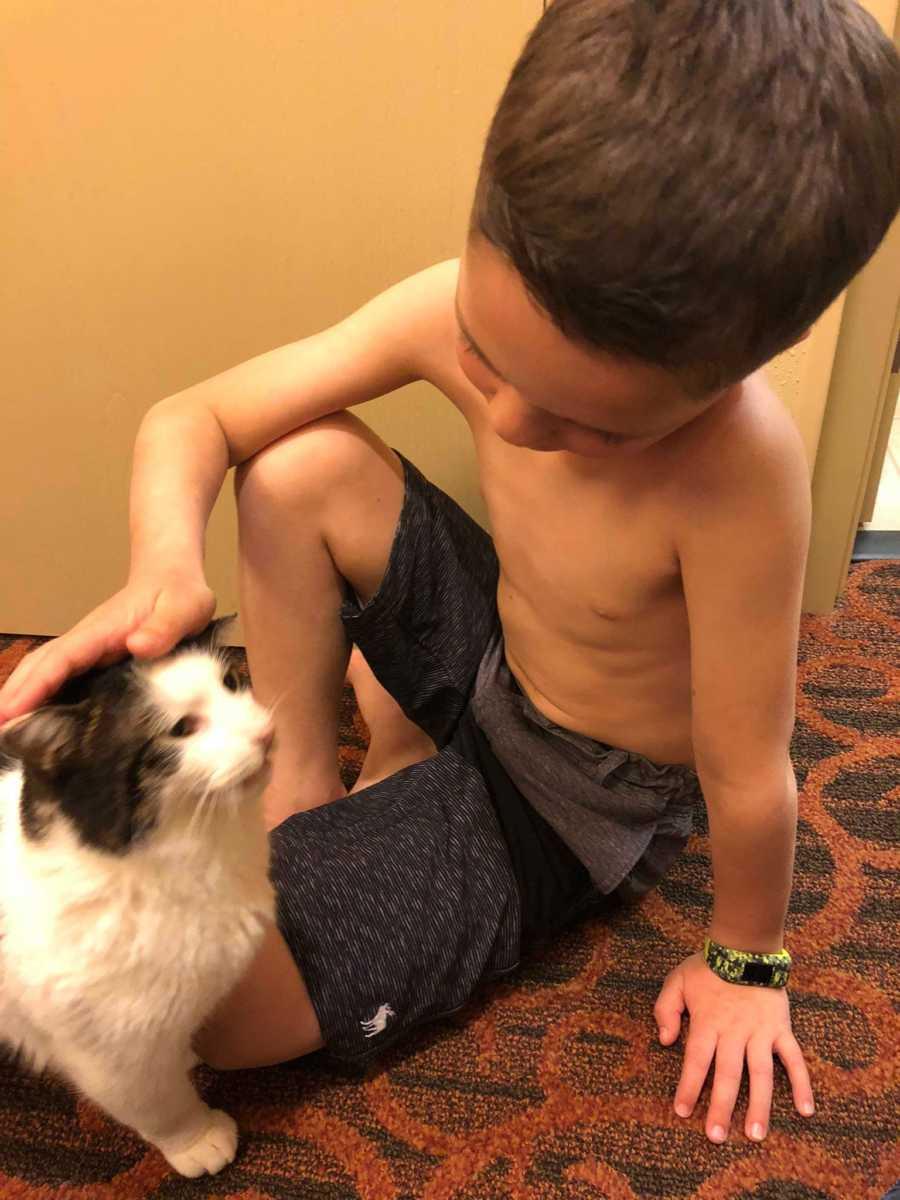 menino fazendo carinho gato