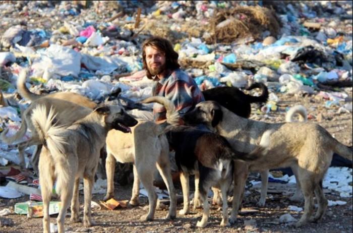 homem com cachorros lixão
