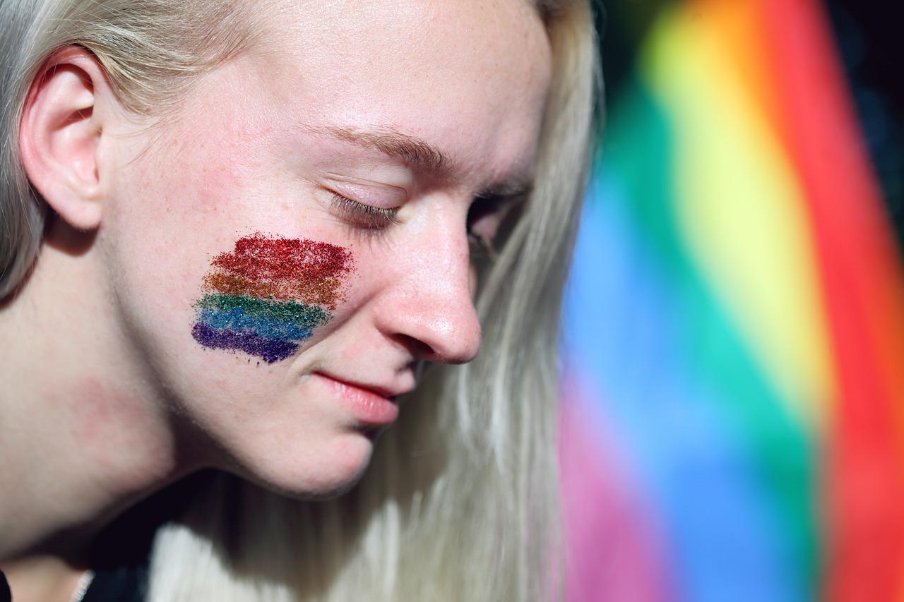 mulher com bandeira arco-íris manifestação lgbt