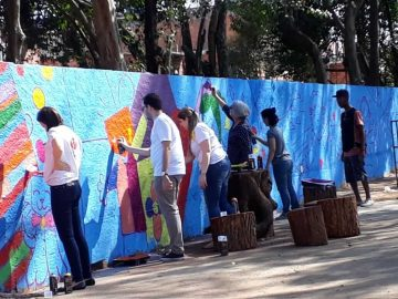 funcionários empresa pintando muro voluntariado