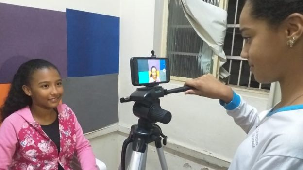 aluna filmando colega projeto escola