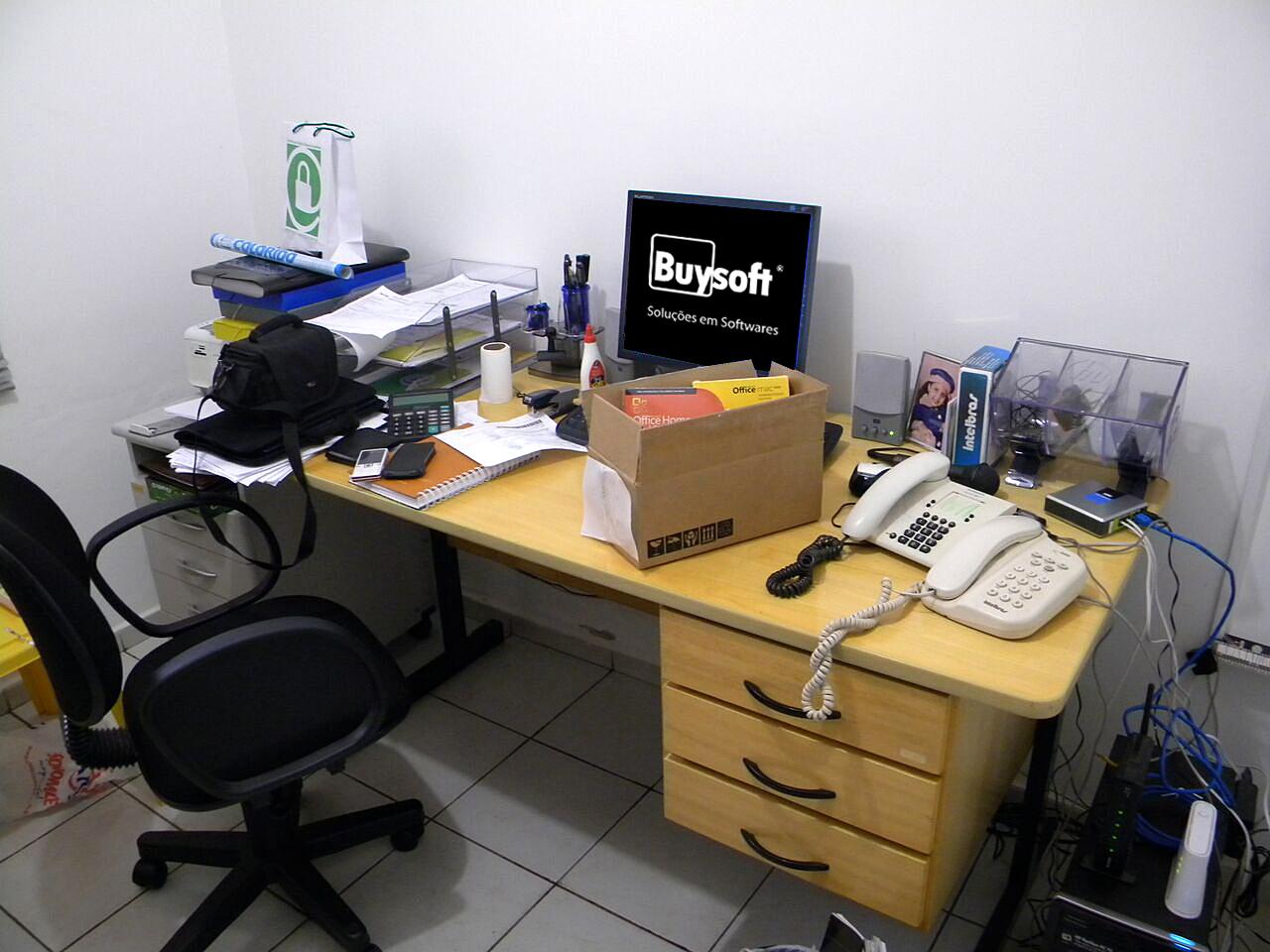 mesa office com telefones e computador com o logo da empresa milionária