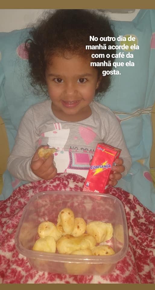 menina comendo pão de queijo cama