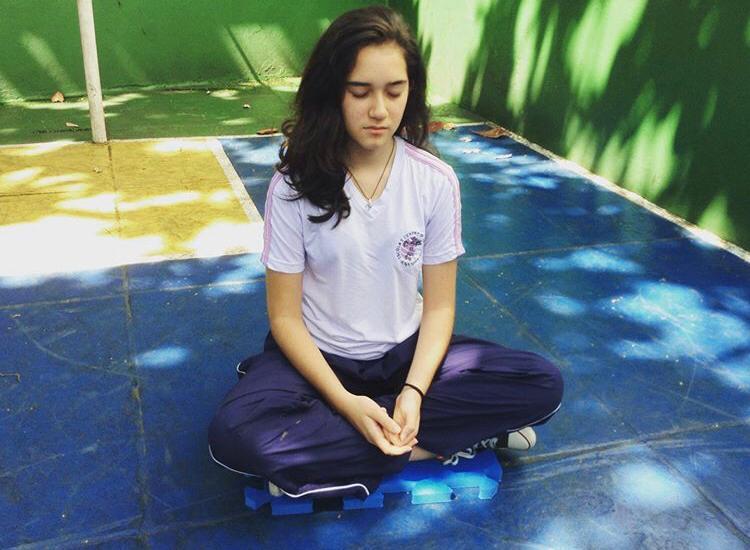 aluna praticando meditação escola
