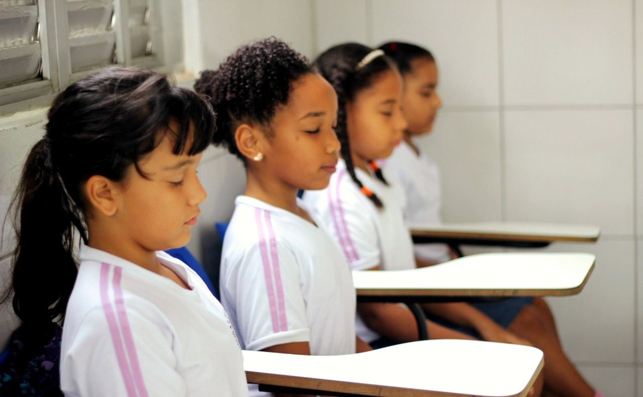 alunas meditam em sala de aula